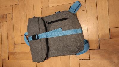 Šedý batoh s modrými popruhy a třemi kapsami, vhodný do města