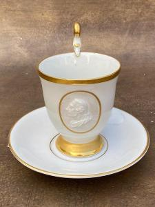 Porcelánový hrnek s podšálkem a miniaturou