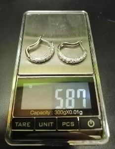 Stříbrné náušnice osazené malými průhlednými kameny.