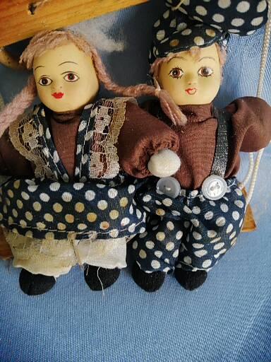 dvě staré,malé panenky na houpačce