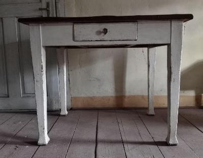 Starý dřevěný stůl se zásuvkou.