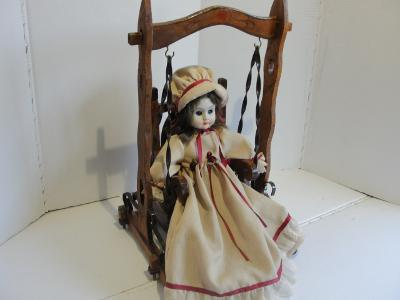 Stará, porcelánová panenka, dřevěná houpačka