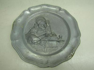 Starožitný kovový nástěnný talíř s reliéfem dívky
